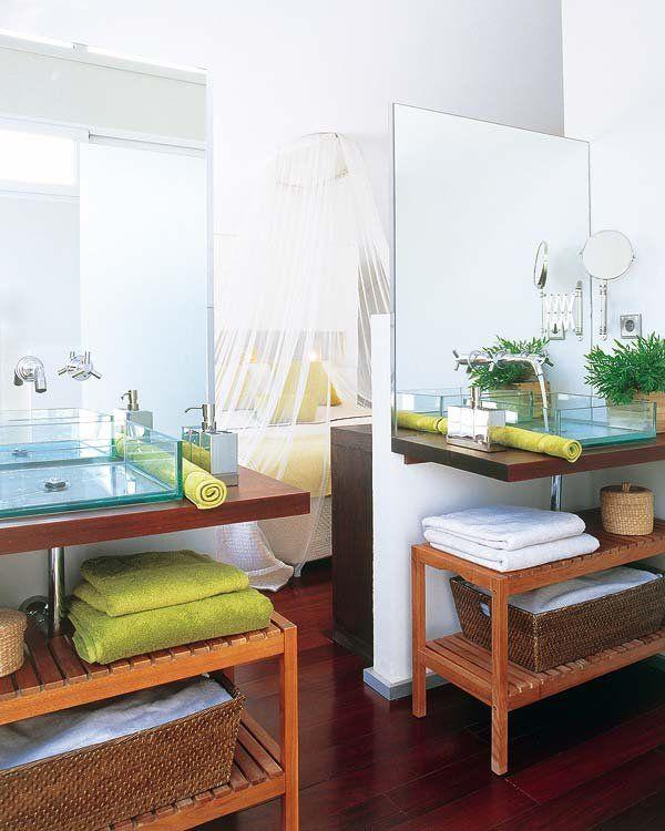 La zona del lavabo ha utilizado el área de lavabos para flanquear el paso al dormitorio. Dos tabiques a media altura sustentan los espejos, a los que se han adosado un par de encimeras voladas de wengé que contrastan con el cristal de los lavabos. Debajo, unos prácticos bancos de Thai Natura sirven de toalleros.