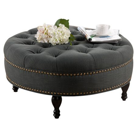 Eucalyptus wood ottoman with tufted grey linen upholstery and foam cushioning. Includes brass-finished casters and decorative nailhead trim.