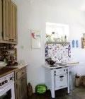 Μια μαντεμένια, ελβετική κουζίνα του 1943 και πλακάκια του Αγγλου καλλιτέχνη Eyers, συναντιούνται στην country style κουζίνα της αντιπαριώτικης κατοικίας.