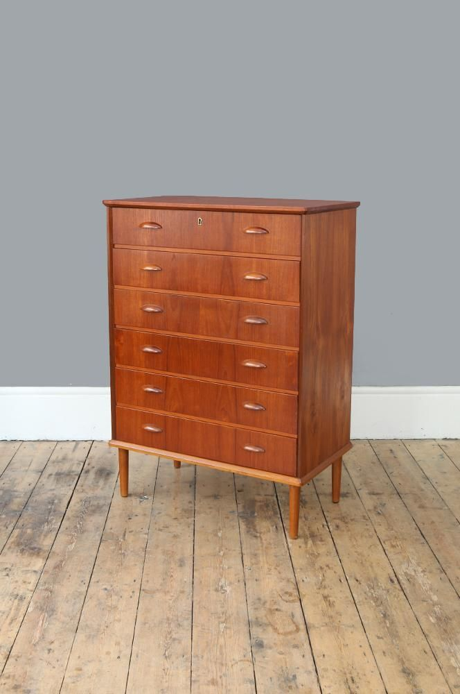 Classic Danish Modern teak chest of drawers with distinctive half moon handles, tapering legs, and six spacious drawers. (Code: F2595)...