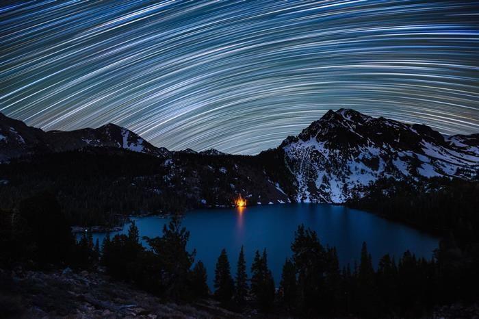 A Inacreditável Beleza do Céu Noturno - O rastro de estrelas ilumina o céu noturno sobre O Lago Verde, na Califórnia. Esses rastros atraem muitos fotógrafos que usam uma técnica de longa exposição para capturá-los. Enquanto supostamente representam o movimento das estrelas no céu, eles estão, na verdade, expondo o movimento do planeta Terra sobre seu eixo.