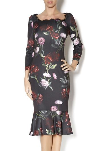 Peony printed, neoprene bodycon dress with 3/4 sleeves and flutter skirt. Features lace detail along neckline. Invisible zip at back. Style with a nude pump and deep lip.