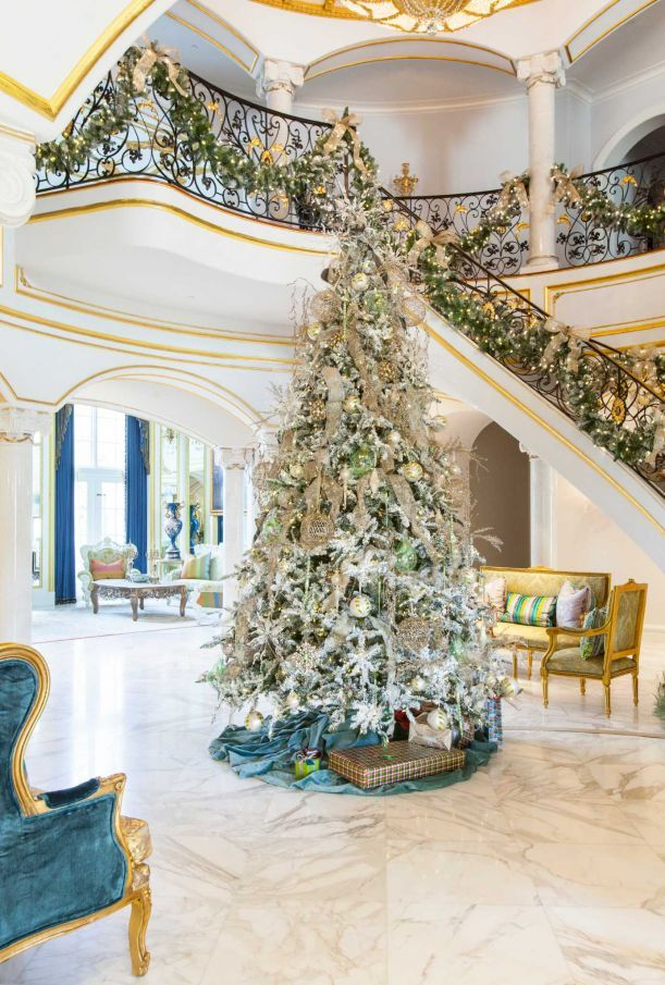 a 12 foot white flocked christmas tree fills the first floor of this grand - 12 Foot Christmas Tree