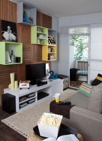 O arquiteto Décio Navarro e a designer Mayra Navarro priorizaram uma decoração funcional e aconchegante: o sofá com assentos retráteis é coberto no braço por uma bandeja de madeira e as cores verde, amarelo e cinza dá um clima jovial ao espaço.