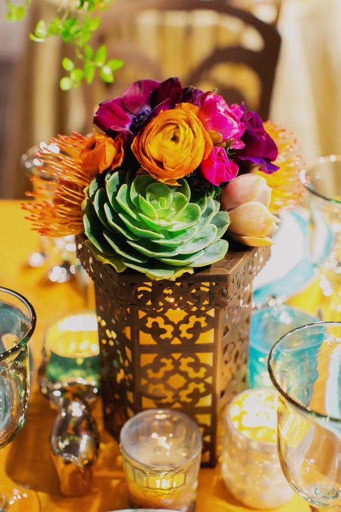 A bold global bohemian centerpiece~ an arrangement of pincushion protea, ranunclus and echeverias atop a candle lantern
