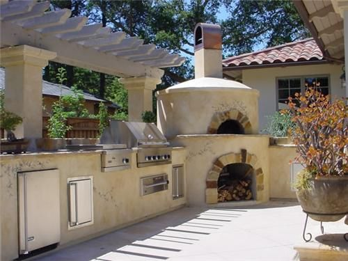 The perfect outdoor kitchen: grill, pizza oven, deep fryer, sink, & beer 'fridge. Who could ask for more?