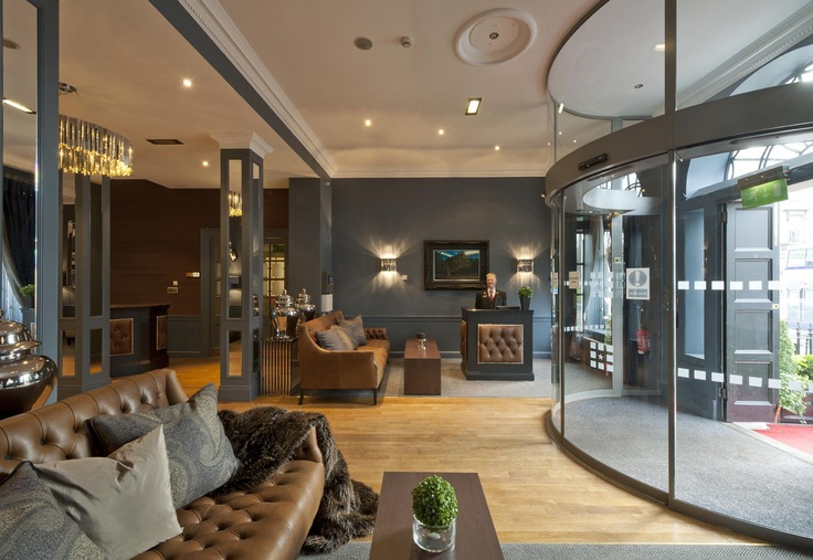 The Roxburghe Hotel, Edinburgh. A stylish hotel reception by Glasgow based Interior Designers, Occa Design.Revolving doors, button backed leather sofas, tan leather, grey blue interior, welcoming spaces
