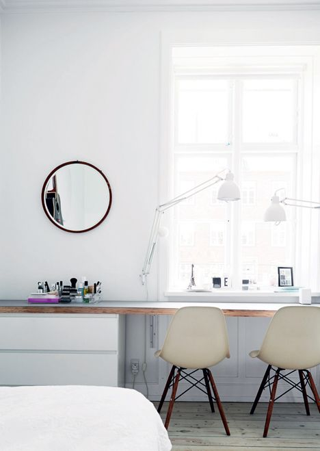 bedroom workspace with round mirror lots of light and Eames chairs - Boligliv