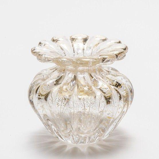 O belo cristal murano surge na Itália em meados do século XIV. Este belo vidro atinge elevadas temperaturas, em torno de 1300 graus, e são esculpidos de forma totalmente artesanal, dando origem a belos vasos, cinzeiros e centros de mesa. Excelente opção para compor a decoração do living ou hall de entrada. Esta bela peça transparente com pó de ouro confere elegância ao seu ambiente. #Vaso #LojaSoulHome