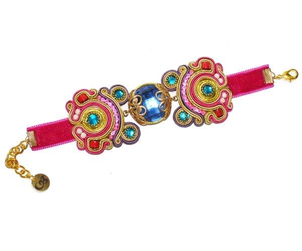 Pulsera de flamenca en tonos rosas, azules y dorados con piedra central facetada en azul. No disponible en otros colores. Realizada a mano.
