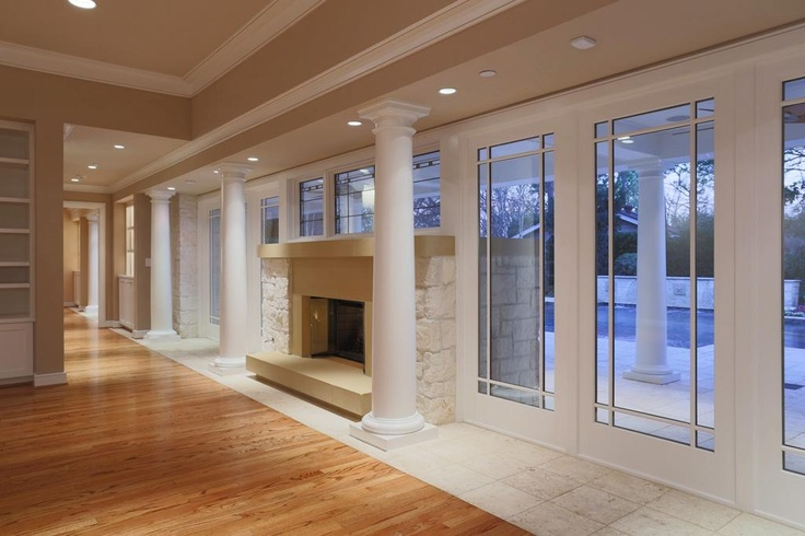 This view shows the transition from the oak hardwood floors to the limestone flooring that beckons you to the outdoor pool area. If you look carefully you can see the columns inside and the columns outdoors uniting the spaces.