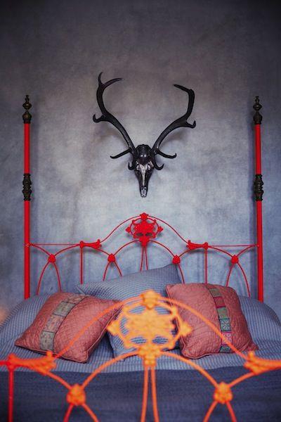 Cool red/orange bed frame. Love the black deer trophy.