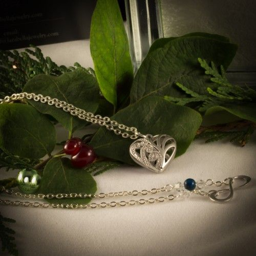 Christmas gift ideas. 614927NSP Brushed silver filigree heart on a 24″ flat cable chain. 614932NSP Brushed siver infinity charm on a 16″ silver plated chain with a Swarovski bicone crystal and mottled blue stone offset into the chain.