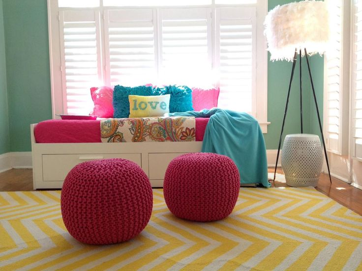 A turquoise wall create a cool backdrop for bold accents, like a yellow chevron rug, woven pink poufs and bright bedding.