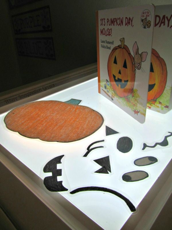 Making pumpkin faces with the children's book It's Pumpkin Day Mouse! A fun fall and Halloween light table activity! Build a Jack-O-Lantern!