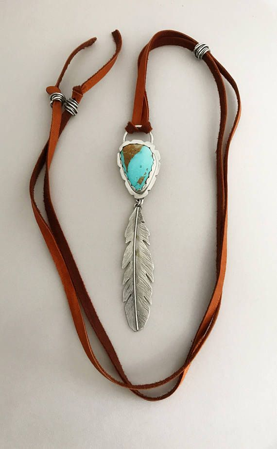 Handcrafted sterling feather that features a Nevada Boulder turquoise. This piece is all hand sawed and textured and the words *brave warrior* are on the back of the feather. I added handmade sterling beads to the deerskin leather to make this pendant adjustable to long or short.