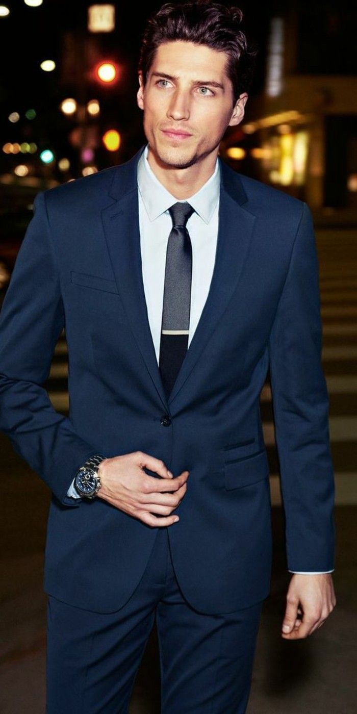3fb8624acd young man wearing a dark blue, two piece suit, with white shirt, and