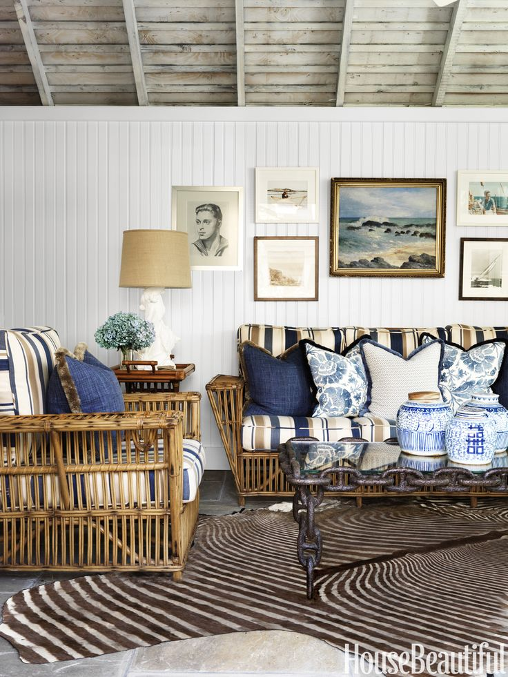 The former garage was transformed into a cozy poolhouse with new beadboard walls, a whitewashed ceiling, and rattan furniture with cushions in Ralph Lauren Home's Dune Point Stripe. - HouseBeautiful.com