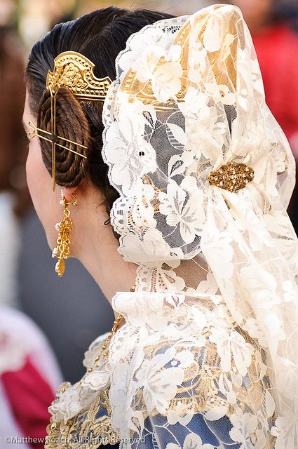 The traditional lace veil headdress worn by 'falleras' as they offer their flowers to Our Lady of the Forsaken during the Fallas Festival in Valencia, Spain.