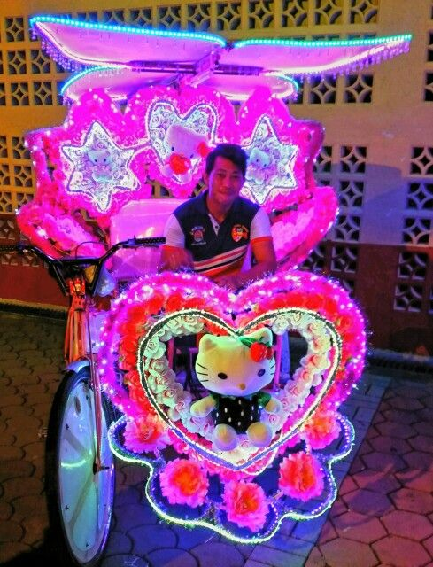 Trishaw rides in Melaka (Melacca) are covered with decorations and lights to attract tourists for rides.