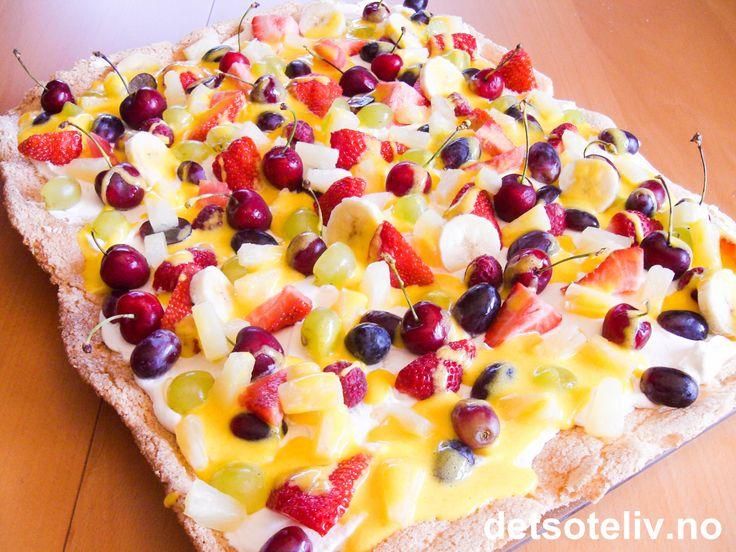 Her har du en virkelig FESTLIG sommerkake! Kaken består av en stor marengsbunn som dekkes med pisket krem og som strøs med massevis av bær og fruktbiter i hulter og bulter. Over dette kaoset ringles det en nydelig, gul saus med ananassmak.