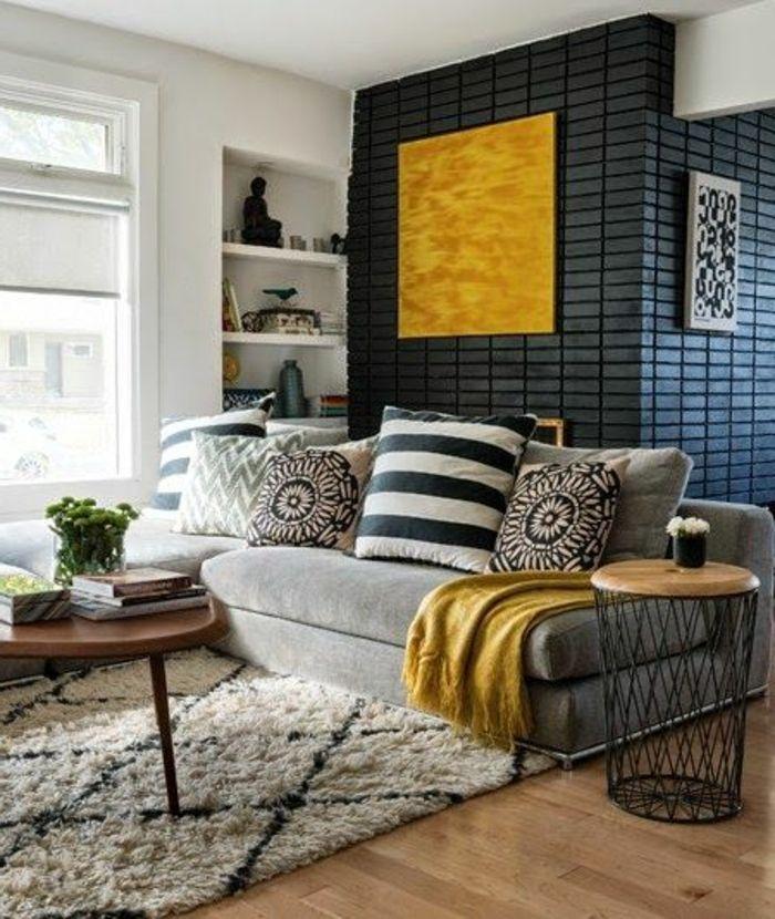 déco jaune, canapé grisn tapis berbèren panneau jaune et déco de briques murales noires