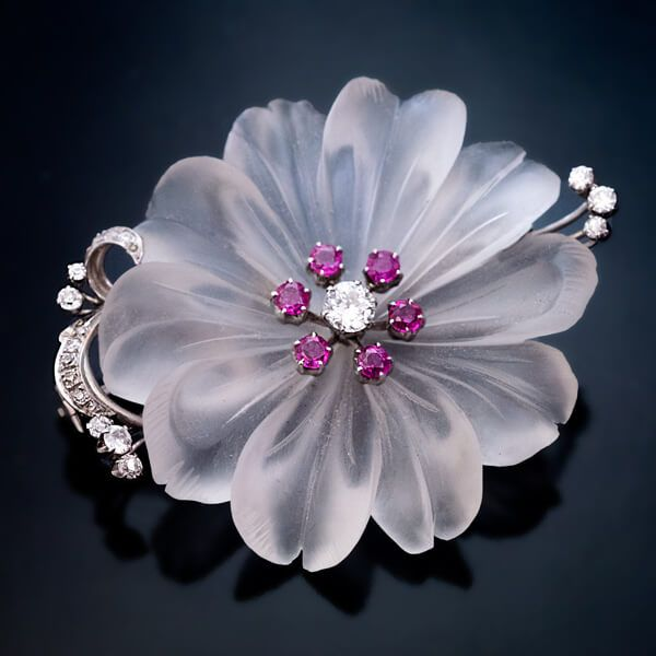 Vienna, 1950s A superbly carved rock crystal flower brooch is mounted in white 14K gold and embellished with diamonds and rubies. The center stone is an ol