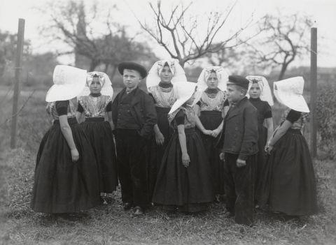 Groep jongens en meisjes in rooms-katholieke Zuid-Bevelandse streekdracht. De kinderen dragen hun zondage dracht of uitgaanskleding. De meisjes dragen over de ondermuts met het oorijzer een 'poepinnemuts' (meisjesmuts). Het tweede meisje van rechts is in de rouw. Door jongens worden zowel petten als hoeden gedragen. Dat door deze kinderen katholieke dracht wordt gedragen is ondermeer te zien aan de wijze waarop de muts is gestreken. 1918-1941 vanAgtmaal #Zeeland #ZuidBeveland #katholiek