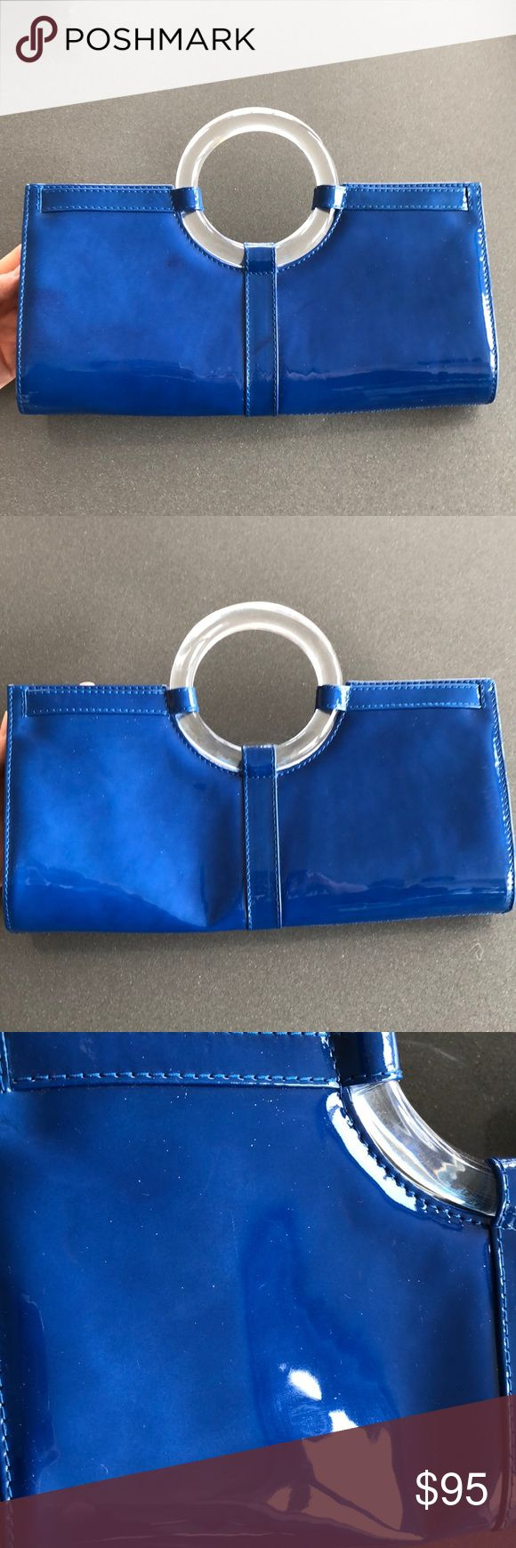 """Stuart Weitzman bag! This bag is amazing! Magnetic closure and funky lucite ring handle. Detachable strap never used and included. Staining in bottom corner from a lipstick. Outside of bag has a couple spots that show """"staining"""". Hard to photo but see up close pictures. Not too noticeable in my opinion. This bag perfectly matches a pair of SW shoes I have listed as well! 11.5"""" x 6"""". Bag is slightly dented right now probably from something sitting on it in the closet but with stuff in it the…"""