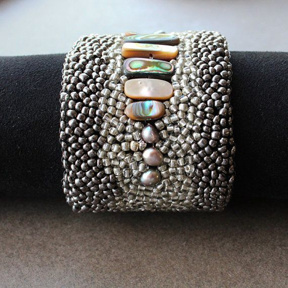Gorgeous cuff bracelet - an organic design with freshwater pearls, abalone nuggets and gold and pewter metallic seed beads - all hand sewn onto a felt base.  Very rock chic!  The lining is soft black suede and the closure is strong black elastic which allows the cuff to fit comfortably on the wrist.  Width 2  Length 7 (but will stretch)      This item will be gift wrapped for you.    Thank You for looking