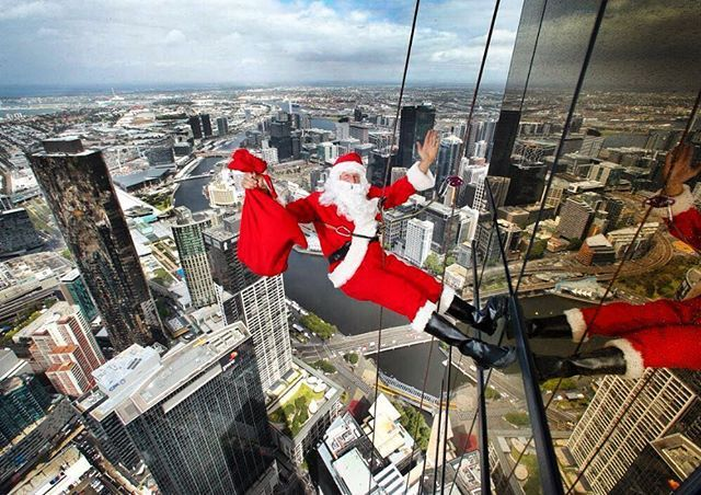 Santa Claus, (aka high rope access climber Chris Davies) with a sack of presents, scales down the Eureka Tower ahead of Christmas Eve at Eureka Skydeck. Picture: David Caird. #Heraldsun #Melbourne #eurekaskydeck @eureka_skydeck #santa #xmas #christmas