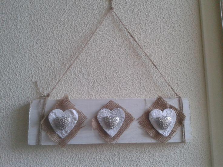 Plank met white wash bewerkt, jute, houte en zilverkleurige hartjes en een stukje touw. Leuk schilderijtje.