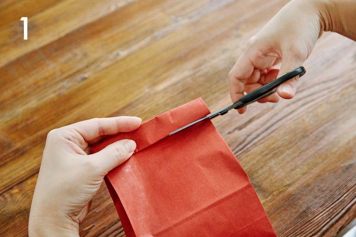 紙袋に品物を入れたら、口を2回折り、両側から袋の幅の3分の1ほどの切り込みを入れます。中に入れたものを切らないよう、注意してください