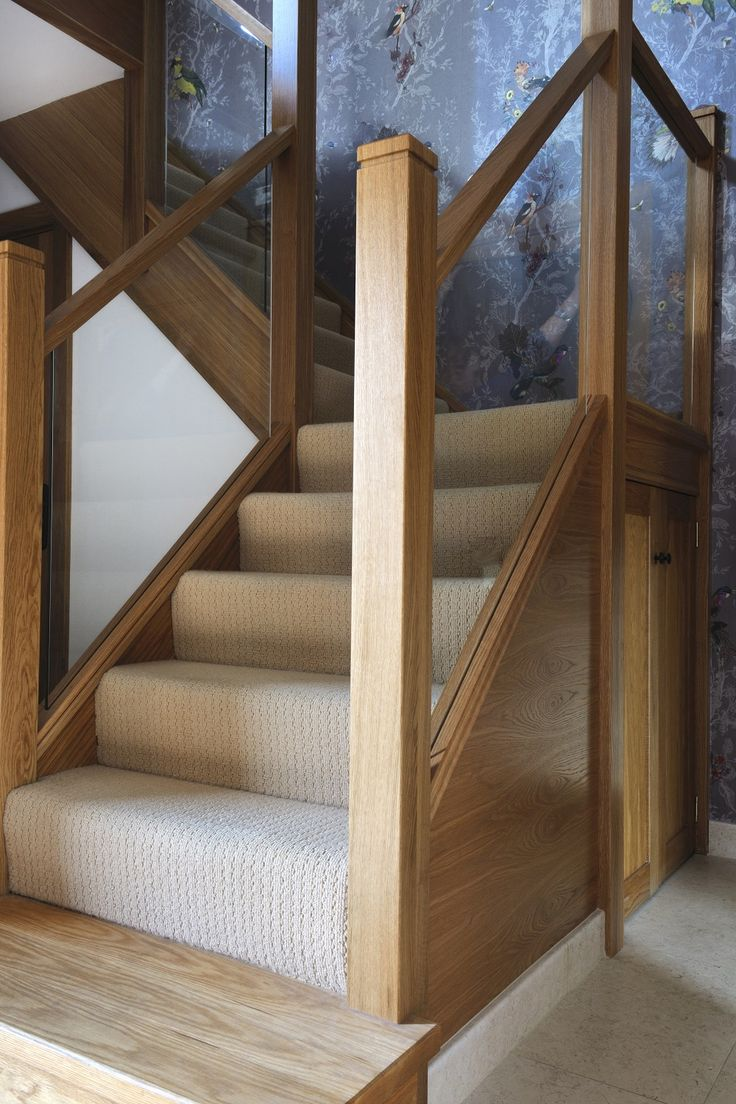 A centrally-positioned mixed modern glass and natural oak staircase with a half-landing turn and gallery landing. Light coloured carpet and wooden feature step.