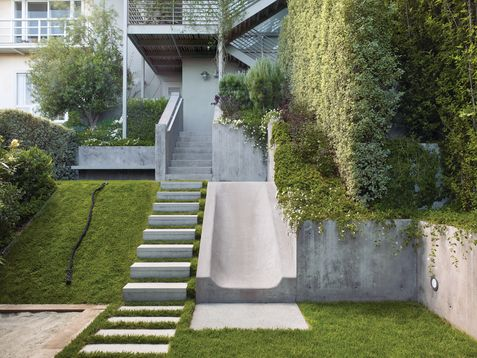 The flat upper terrace, which hosts a cantilevered concrete bench and is primarily where the parents sit and watch activities unfold, leads into a steep slope with three side-by-side elements: steps, a sloped lawn, and a concrete slide.
