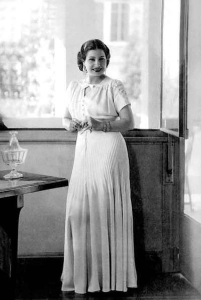The 1920s: Umm Kulthum (1898-1975). She was active in her career from the 1920s through the 1970s. Kulthum was an internationally famous singer, songwriter, and film actress. Kulthum is glamorously showing off her modest yet chic dress while posing for this photograph. She is demonstrating the style of her era by having her hair in an up-do while wearing a long sleek dress.