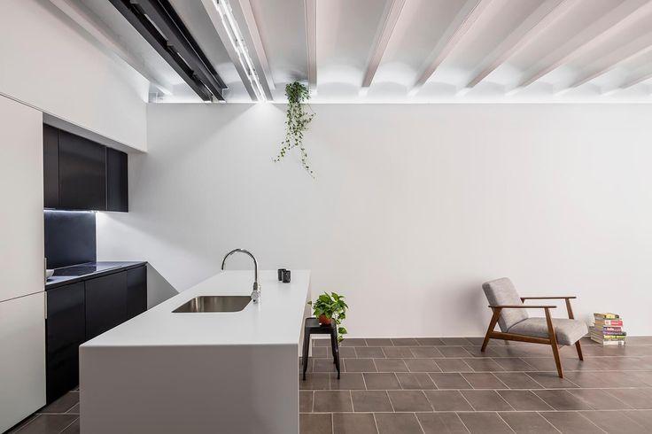Cozinha reformada com piso original cinza, bancada em ilha bancada nova armários cinza escuro, banqueta tolix grafite e paredes brancas. Apartamento Minimalista em Barcelona por RAS Studio