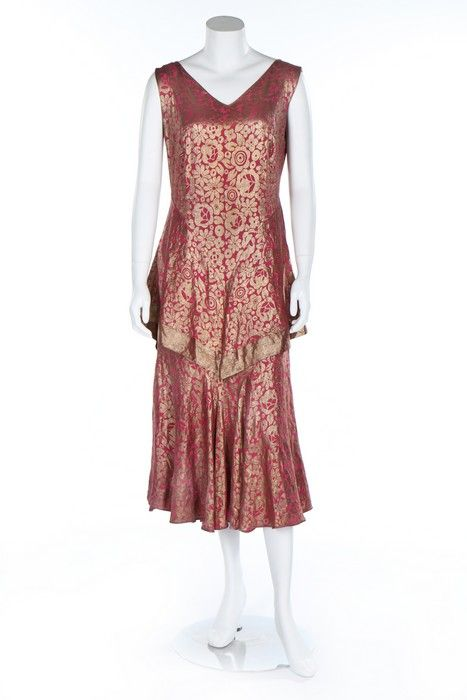 A pink and gold damask satin evening ensemble, circa 1929.  A pink and gold damask satin evening ensemble, circa 1929. the dress with gold edged tiered over-skirt which forms a trained panel at the back, matching jacket with shirring to sleeves, bust 92-97cm, 36-38in (2).  Estimate:£150 - £250