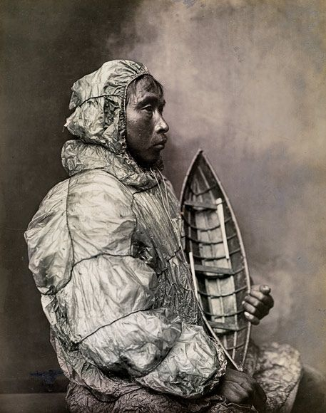 Sitting in a Nome, Alaska, photo from early 1900s, an Eskimo man in an anorak/parka fashioned of walrus intestine. Impermeable when wet and easy to come by for the sea-focused people, the material was prepared by air curing, then sliced and sewn with a waterproof stitch—the same as used on watercraft, including the model of an umiak he's holding. a family boat for women, gear and dogs, or whalehunting. The anorak's extra material at the hem functioned as a spray skirt when sitting in the…