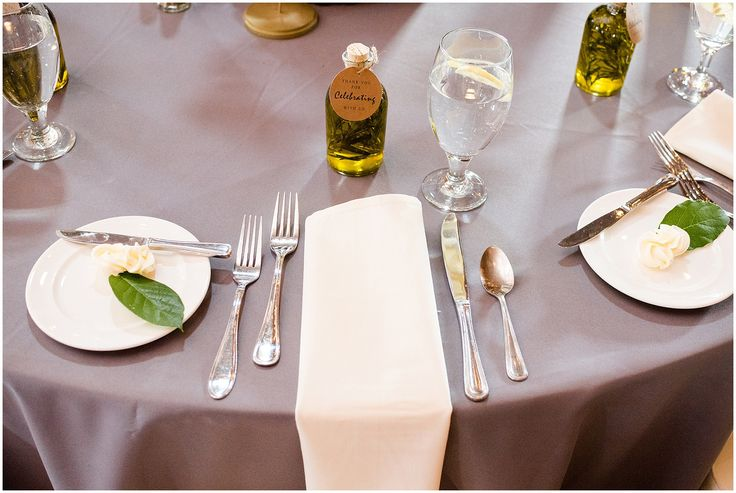 Dinner table set with grey table cover, white runner napkin, silverware, glass of water with lemon, bread plate with butter accented with greenery, and a bottle of olive oil with rosemary as a guest gift at The Farm at Lake Cottrell Wedding in Union Dale Pennsylvania by Jes & Mike Photography - Wedding Photographers in Northeastern PA - Lake Ariel, PA