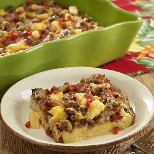 Hawaiian sweet bread topped with cheese, breakfast sausage, red bell pepper, pineapple and egg-milk mixture for a Hawaiian sausage casserole