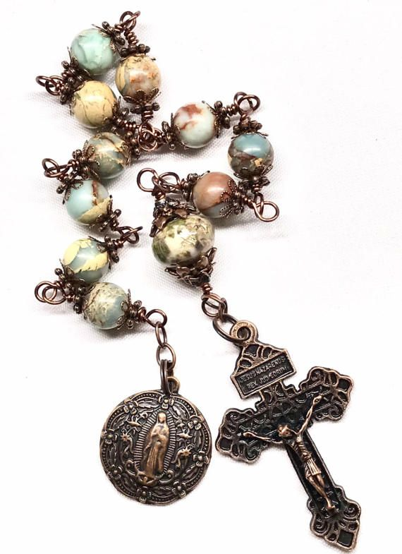 This beautiful Tenner is made to last a lifetime. I used a 2 Inch Copper Pardon Crucifix, a one inch Copper Our Lady of Guadalupe Medal, Copper Oval Links Chain, and Copper Wire. I also used 46 total copper bead caps (used in layers) to cover these exquisite multi-colored marbled Impression Jasper Beads. I used ten 10 mm beads, and one larger Impression Jasper Roundel for the Our Father bead. The crucifix is beautifully detailed, with a message on the back. JASPER: a semi-precious stone…