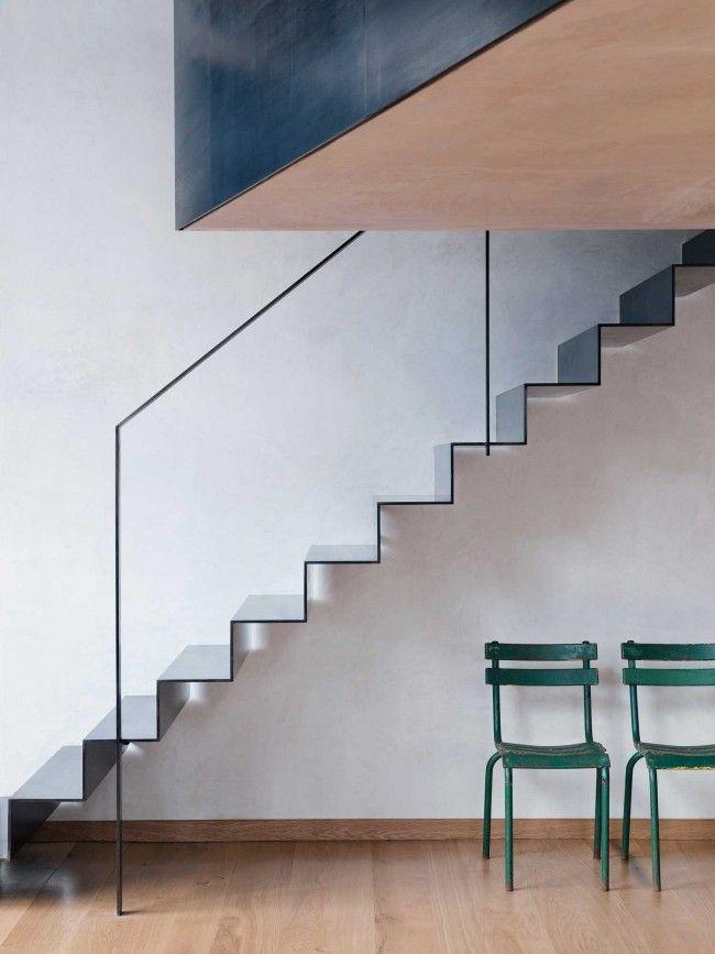 Te gekke industriële loft in oud Londens pakhuis met een dun uitgevoerde stalen trap