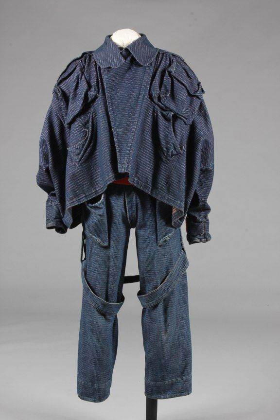 * Vivienne Westwood blue and red denim man's suit, probably 'Witches' collection, Autumn-Winter, 1982-83, World's End label to trousers, comprising: voluminous jacket with curving hemline, massive crumpled patch pockets to the shoulders, diagonal vented pockets to the waist front, red velcro straps to the cuffs, matching belt; the bondage trousers zip fastened from front to back, large white zips to rear legs, large patch pockets to the hips