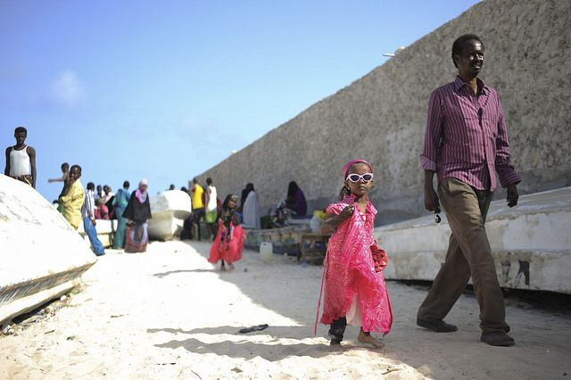 A little girl and her father walk on Lido beach in Mogadishu, Somalia, during Eid al-Fitr, the Muslim holiday marking the end of Ramadan.