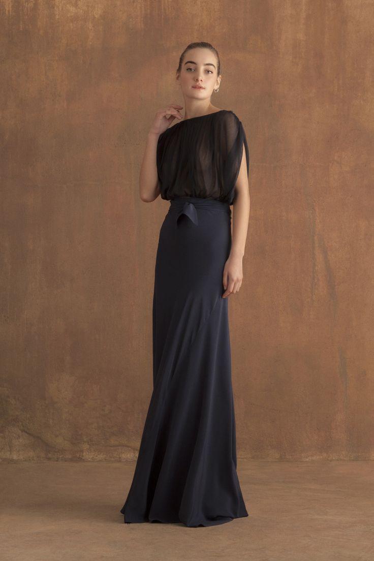 Falda larga realizada en seda cortada al biés en color English blue. La falda no lleva botones y se cierra atada a la cintura. El lazo se puede llevar en la parte delantera o trasera. En la imagen, combinada con el top Fortuny de tul de seda con cuello a caja en la parte delantera …