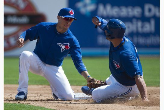 Toronto Blue Jays shortstop Ryan Goins, left, tags out Kevin Pillar on a steal attempt at second base during third inning intrasquad game action in Dunedin, Fla., on Monday.