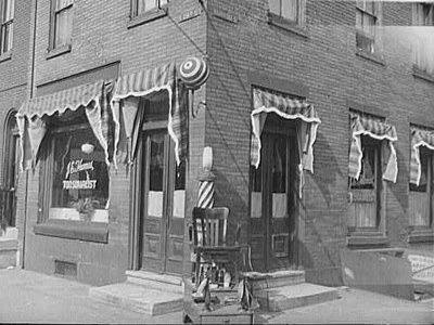 This picture was taken by Paul Vanderbilt in Spring, 1937, during the depths of the Great Depression. The barbershop, with the shoeshine stand out front, was on the corner of 19th and Bainbridge Streets in Philadelphia, Pennsylvania. The striped ball at the top spins and is very unusual.