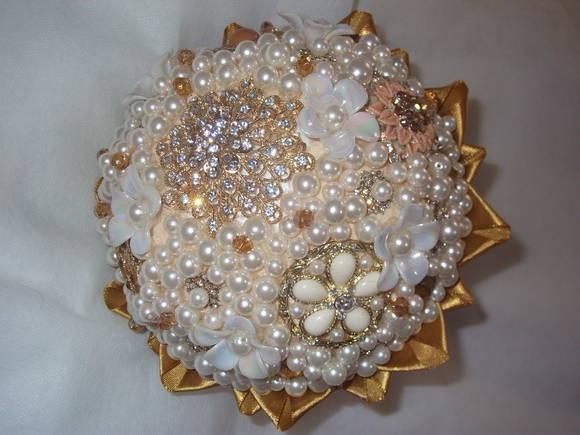 Buquê de broches dourados, com detalhes em pérolas e cristais. Cetim dourado.