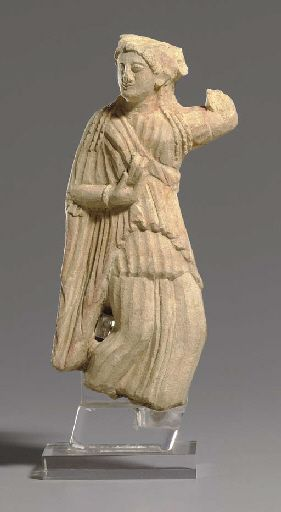 Cypriot limestone dancing Maenad, late 6th-early 5th century B.C. The sinuous figure clad in a finely pleated chiton and himation with swallow tail folds along the edge, her body portrayed in an S shape in movement,  holding a krotalon castanet in her right hand, adorned with a bracelet, her hair arranged in snail like curls across her forehead, 17.8 cm high. Private collection